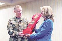 "Brig. Gen. Patrick D. Frank, 1st Infantry Division and Fort Riley acting senior commander, presents Phyllis Fitzgerald, Junction City mayor, with a wooden ""Big Red One"" March 15 following the Women's History Month observance at Riley's Conference Center."