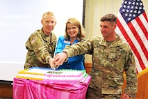 LEFT TO RIGHT: Brig. Gen. Patrick D. Frank, 1st Infantry Division and Fort Riley acting senior commander, Junction City Mayor Phyllis Fitzgerald and Lt. Col. Andrew Beyer, 1st Combat Aviation Brigade, 1st Inf. Div., rear detachment commander, cut the cake for Women's History Month at Riley's Conference Center March 15.