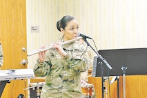 Spc. Florida Rodriguez, a flutist with the 1st Inf. Div. Band, plays March 15 during the Women's History Month observance at Riley's Conference Center. Rodriguez is the jazz ensemble's newest member. Rodriguez joined the Army in December 2014 and is working on her masters in music performance and plans to go on to complete a Ph.D. in music so she can teach.