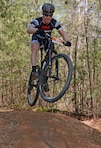 A mountain bicyclist goes airborne during the Six Hours of Warrior Creek mountain bike race at the Wilmington District's W. Kerr Scott Dam and Reservoir in Wilkesboro, N.C. (See article below. File photo by Hank Heusinkveld)