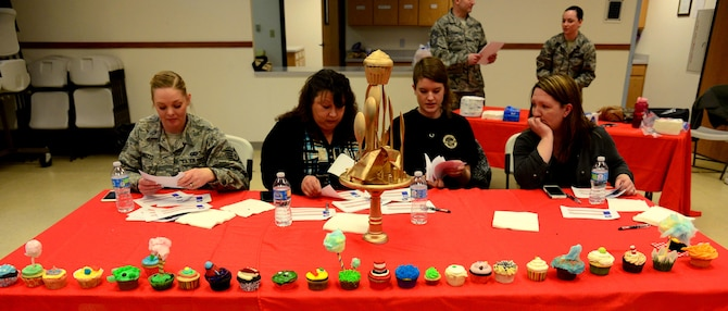 Judges discusses competition results at the 341st Missile Wing's first cupcake war held April 3, 2017, at Malmstrom Air Force Base, Mont. Four judges tasted quartered bits of 26 different cupcake recipes submitted by 18 different teams, judging taste and creativity. (U.S. Air Force photo/Senior Airman Magen M. Reeves)