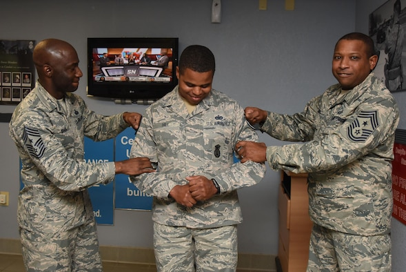 Chief Master Sgts. Vegas Clark, 81st Training Wing command chief, and Farrell Thomas, 2nd Air Force command chief, participate in a Stripes for Exceptional Performers promotion ceremony for Staff Sgt. Courtney Hill, 81st Security Forces Squadron pass and ID NCO in charge, at the visitors center March 30, 2017, on Keesler Air Force Base, Miss. Hill was STEP promoted to the rank of technical sergeant. In the past year, Hill oversaw the issue of 20,000 passes and coordinated entry for multiple base events. His hard work and dedication was acknowledged when he won 81st Mission Support Group NCO of the year for 2016. (U.S. Air Force photo by Kemberly Groue)