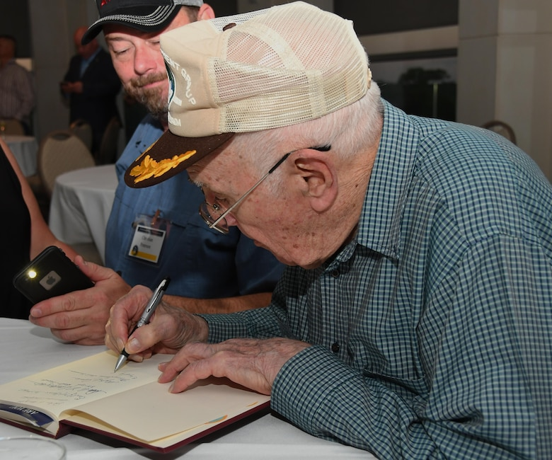 A 307th Bomb Wing alumni signs a book on the history of the 307th Bombardment Group during a reunion icebreaker event at the Shreveport Convention Center, Shreveport, La., March 30, 2017. The 307th BW hosted a reunion to celebrate the 75th anniversary of the unit and included alumni from wars such as World War II, the Korean War, Vietnam and the Cold War. (U.S. Air Force photo by Staff Sgt. Callie Ware/Released)