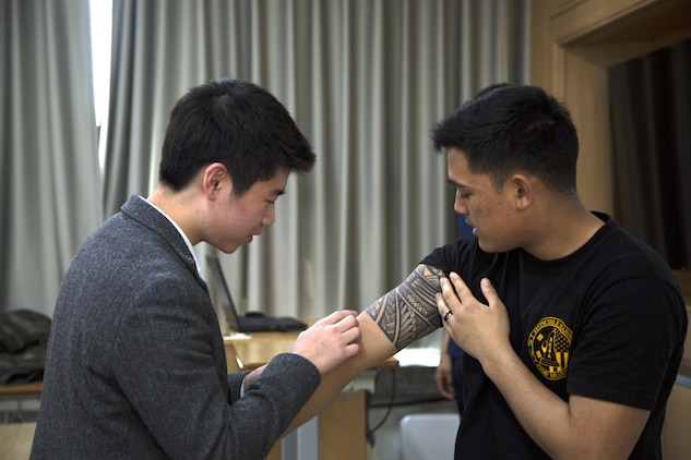 A student at Ocheon high school admires Cpl. Jarred Sagadraca's tattoo March 30 in Pohang, South Korea. Sagadraca honors his heritage with a Polynesian-styled tatoo. Tattoos have become increasingly popular in South Korea in recent years, but the law requires them to be done at a hospital. This has made them rare and the students were excited to see one up close. Sagadraca is a motor transport mechanic with Combat Logistics detachment 333, Combat Logistics Battalion 4, Combat Logistics Regiment 3, 3rd Marine Logistics Group, III Marine Expeditionary Force. (U.S. Marine Corps photo by Cpl. Jessica Collins)