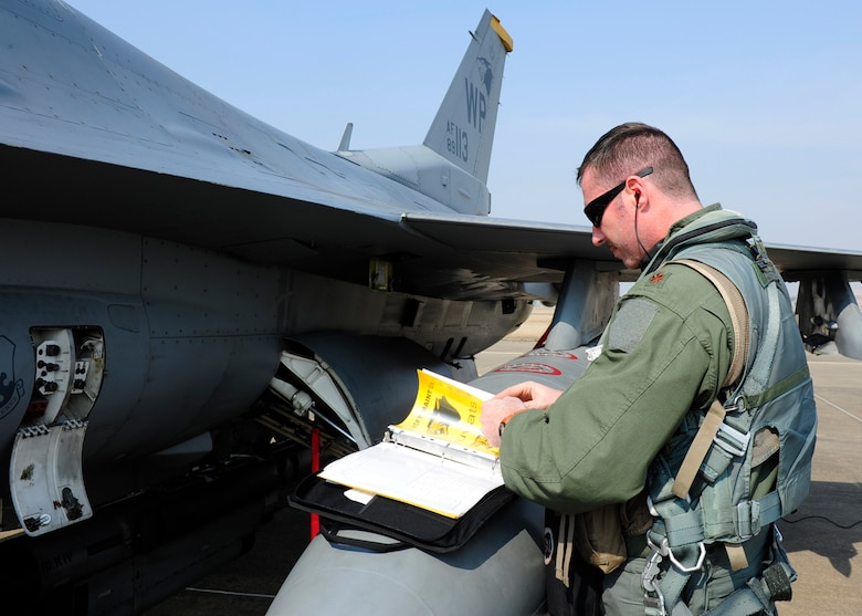 U.S. Air Force Maj. Michael Mullin, 80th Fighter Squadron director of operations, goes over a preflight checklist at Seosan Air Base, Republic of Korea during Buddy Wing 17-3, March 30, 2017. Buddy Wing exercises are conducted multiple times throughout the year to sharpen interoperability between U.S. and ROK forces. (U.S. Air Force photo/Staff Sgt. Chelsea Sweatt)