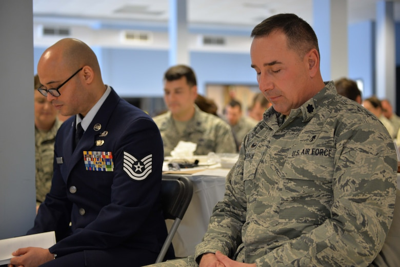 From the left, Tech. Sgt. Siddartha Sosa Rodriguez, a member of the 157th Air Refueling Wing Chaplin's Corps, and Lt. Col. Fred Brennan, 157th Medical Group commander, bow their heads during a prayer for the nation at the Commanders Annual Prayer Breakfast, April 2, 2017, Pease Air National Guard Base, N.H.(N.H. Air National Guard Photo by Senior Airman  Ashlyn J. Correia)