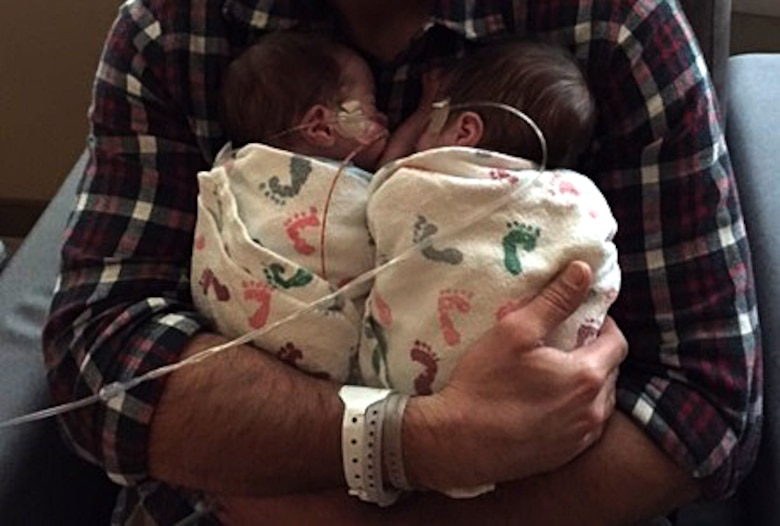 COLORADO SPRINGS, Colo. – John Aagaard, spouse of Staff Sgt. Susan Edwards-Aagaard, 21st Operations Support Squadron intelligence analyst, holds his newborn twins in Colorado Springs, Colo., Oct. 4, 2015. The twins were born seven weeks early with many health issues, but get stronger as each day passes. (Courtesy photo)