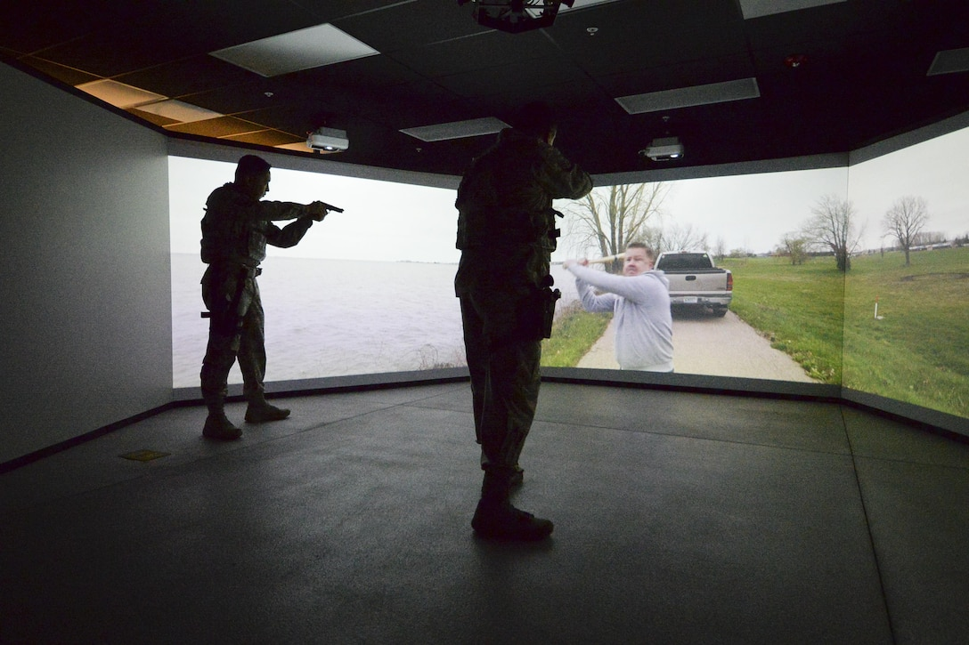 U.S. Air Force Staff Sgt. Ricardo Cuellar and Master Sgt. Alex Orino of the 129th Security Forces Squadron demonstrate the multitude use of the Multiple Interactive Learning Objectives (MILO) Range at Moffett Air National Guard Base, Calif., Feb. 15-2017.  The MILO Range, is a modular area designed to accommodate a multitude of training scenarios to law enforcement agencies. (U.S. Air National Guard photo by Senior Airman Zachiah Roberson/released)