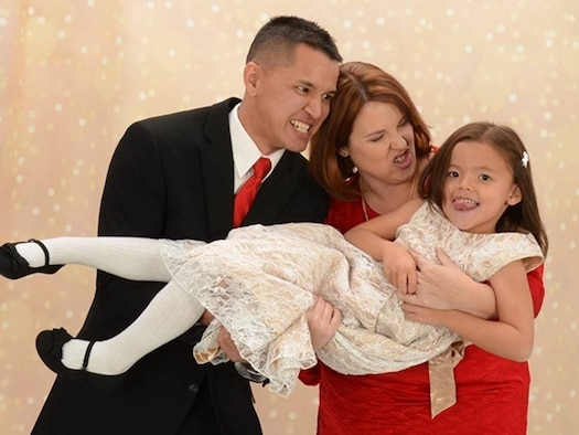 COLORADO SPRINGS, Colo.— Staff Sgt. Richard Espinosa, 10th Surgical Operations Squadron NCO in charge of MRI stationed at the U.S. Air Force Academy, Colo., and Shellie-Anne Espinosa, 21st Space Wing public affairs specialist at Peterson AFB, Colo., play around with their daughter, Rebekah Espinosa, during a Christmas photo shoot in Colorado Springs, Colo., Nov. 13, 2016. The Espinosas' lives changed for the better when their daughter was able to receive the correct therapies to help her learn after being diagnosed with autism spectrum disorder in 2016. (courtesy photo)