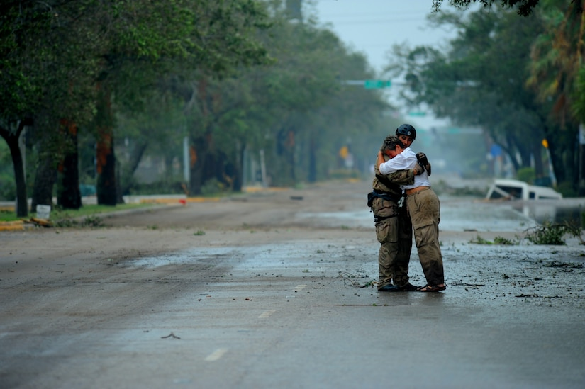 U.S. Air Force Pararescueman Staff Sgt. Lopaka Mounts, assigned to the 331st Air Expeditionary Group receives a hug from a resident during search and rescue operations after Hurricane Ike,  September 13, 2008. This photograph was provided by the 1st Combat Camera Squadron to showcase world events they have documented throughout the past 25 years.