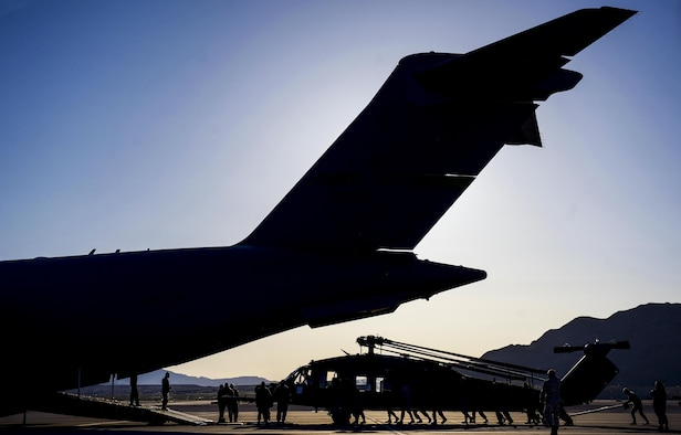 Airman push an HH-60 Pave Hawk assigned to the 34th Weapons Squadron, into position as it is loaded into a C-17 Globemaster III assigned to the 57th Weapons Squadron, McChord Air Force Base, Wash., March 28, 2017. The C-17 Globemaster has the load capacity to haul two HH-60 Pave Hawks. (U.S. Air Force photo by Airman 1st Class Kevin Tanenbaum/Released)