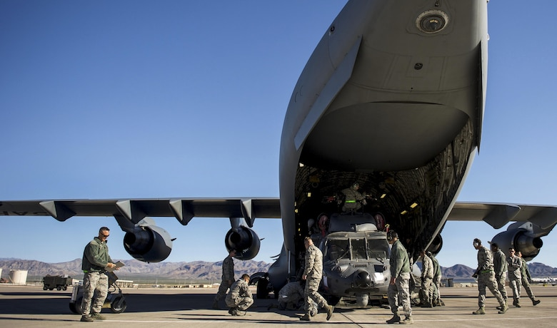 Airmen, 34th Weapons Squadron, finish loading the first of two HH-60 Pave Hawks into a C-17 Globemaster III assigned to the 57th Weapons Squadron, McChord Air Force Base, Wash., March 28, 2017. The Pave Hawk is a highly modified version of the Army Black Hawk helicopter, which features an upgraded communications and navigation suite. (U.S. Air Force photo by Airman 1st Class Kevin Tanenbaum/Released)