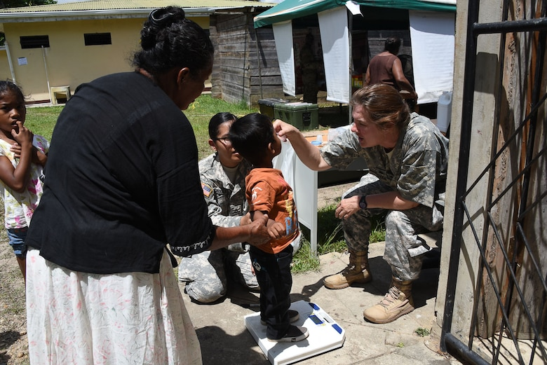 Lt. Col. Rhonda Dyer, a community health nurse with Joint Task Force-Bravo's Medical Element, gives de-working medication to a local Nicaraguan child during a Medical Readiness Exercise held in the village of Waspam March 28-31. Pfc. JoAnna Rodriguez helps to weigh all the children at the Preventive Health Station. (U.S. Air Force photo by Capt. Denise Hauser)