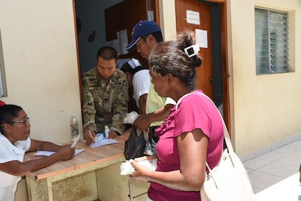 Capt. Ken Lau, Joint Task Force-Bravo's Medical Element Pharmacy Technician, hands out medicine to Nicaraguans of the local village of Waspam during a three day Medical Readiness Exercise March 28-31. More than 1,600 patients were seen over the few days. (U.S. Air Force photo by Capt. Denise Hauser)