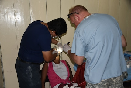 Sgt. 1st Class Christin Beck, dental technician, and Dr. Wilmer Amador, dentist, extract a tooth from a local Nicaraguan from the Waspam village during a three-day Medical Readiness Exercise March 28-31. Personnel from the JTF-Bravo's Medical Element worked side by side with local nurses and physicians, as well as Nicaraguan soldiers to provide the population with immunizations, preventive medicine, dental services, basic medical care and pharmacy services. Over the course of the exercise there were 360 tooth extractions. (U.S. Air Force photo by Capt. Denise Hauser)