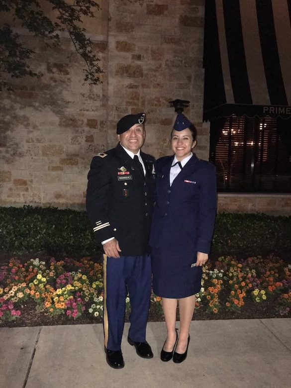 U.S. Army Col. Michael Rodriguez stands by his daughter, U.S. Air Force 2nd Lt. Scarlett Rodriguez after her commissioning ceremony. Colonel Rodriguez surprised his daughter with a traditional engraved sabre after her commissioning ceremony, an odd gift to unwrap in the middle of an Italian restaurant.