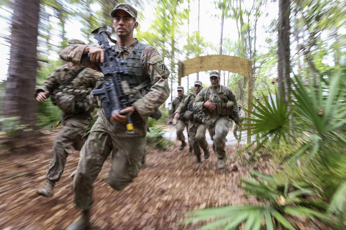 Soldiers carry weapons as they race through trees and plants.