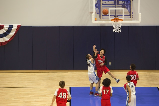 A Marine Corps Air Station Iwakuni basketball player attempts to block a Higashi Junior High School player's shot during the Friendly Basketball Tournament at MCAS Iwakuni, Japan, March 25, 2017. The tournament was composed of six junior high school teams and bridged the gap of two cultures by helping children make new friends through a common interest. (U.S. Marine Corps photo by Pfc. Stephen Campbell)