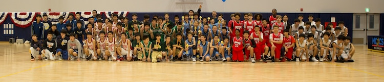 Participating teams pose together after the Friendly Basketball Tournament at Marine Corps Air Station Iwakuni, Japan, March 25, 2017. The tournament was composed of six junior high school teams  and bridged the gap of two cultures by helping children make new friends through a common interest. (U.S. Marine Corps photo by Pfc. Stephen Campbell)
