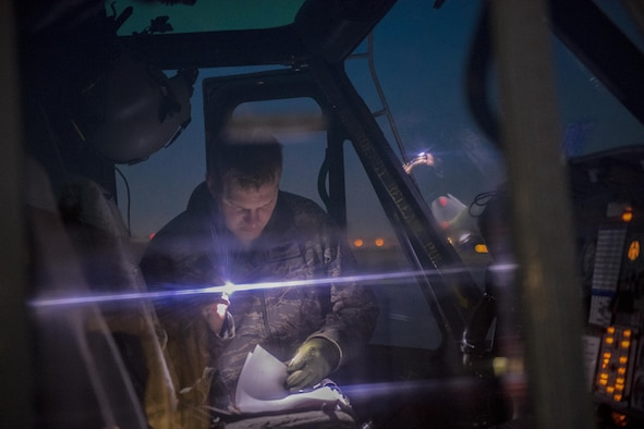 Capt. Jonathan W. Coffey, 459th Airlift Squadron pilot, performs final checks prior to a night hoist training exercise April 4, 2017, at Yokota Air Base, Japan. The hoist allows the 459 AS to conduct rescue missions in small, tight areas throughout the Kanto Plains. (U.S. Air Force photo by Airman 1st Class Donald Hudson)