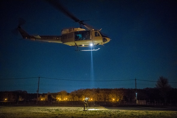 Capt. Lance M. Stafford, 36th Airlift Squadron pilot, is lifted into UH-N1 Iroquois during a 459th Airlift Squadron night hoist training exercise April 4, 2017, Tokyo, Japan. The aircrew performed hoist insertion and extraction from 25-35 feet above ground. (U.S. Air Force photo by Airman 1st Class Donald Hudson)