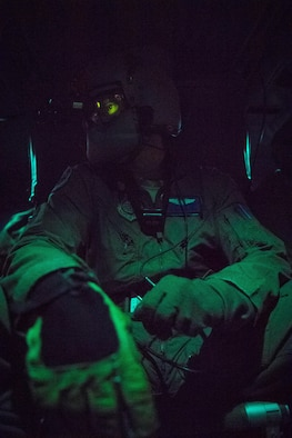 Staff Sgt. Nicholas A. Poe, 459th Airlift Squadron special mission's aviator, looks out the window of a UH-N1 Iroquois through night vision goggles during a night hoist training exercise April 4, 2017, Tokyo, Japan. The aircrew trained with night vision goggles in the event a mission must be conducted at night in the future. (U.S. Air Force photo by Airman 1st Class Donald Hudson)