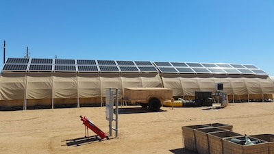 Part of the Air Force Research Laboratory's forward operating base of the future demonstration is one complete expeditionary microgrid system, pictured here during Basic Expeditionary Airmen Skills Training at Lackland Air Force Base in San Antonio, February 25, 2016. Monocrystalline silicon solar panels are placed on top of each tent for energy production. A trailer, at center, holds the hardware, software and lithium ion batteries that form the smart grid and provide energy backup should the grid fail. The project evaluates energy reduction technologies such as shelter insulation and efficient heating, ventilation and air conditioning systems. Air Force photo by Donna Lindner