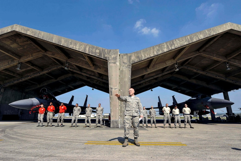 U.S. Air Force Tech. Sgt. Benjamin Bouvy, 18th Aircraft Maintenance Squadron weapons load standardization crew member, gives the opening remarks of a quarterly weapons load competition April 3, 2017, at Kadena Air Base, Japan. The competition was held between the 44th and 67th Aircraft Maintenance Units for quickest and most accurate loading of weapons on their respective aircraft. (U.S. Air Force photo by Naoto Anazawa/Released)