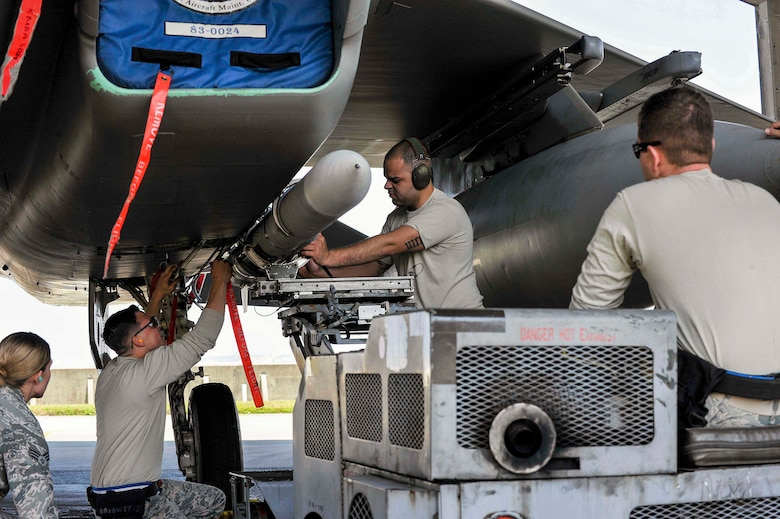 A U.S. Air Force weapons load crew team from the 44th Aircraft Maintenance Unit secure an AIM-120 advanced medium-range air-to-air missile to an F-15 Eagle fighter aircraft during a quarterly weapons load competition April 3, 2017, at Kadena Air Base, Japan. The competition evaluated safety, reliability and effectiveness while adhering to technical data and explosive safety. (U.S. Air Force photo by Naoto Anazawa/Released)