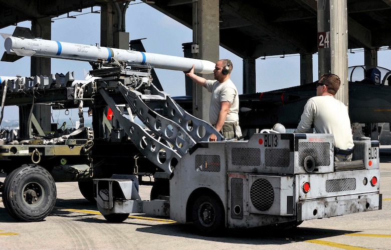 A U.S. Air Force weapons load crew team from the 44th Aircraft Maintenance Unit uses an MJ-1C lift truck to transport an AIM-120 advanced medium-range air-to-air missile to an F-15 Eagle fighter aircraft during a quarterly weapons load competition April 3, 2017, at Kadena Air Base, Japan. Weapons load competitions are conducted quarterly to keep Airmen sharp and recognize superior performers. (U.S. Air Force photo by Naoto Anazawa/Released)