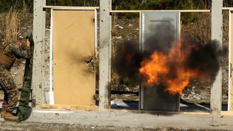Marines detonate an explosive charge on a door during a breaching exercise at Marine Corps Base Camp Lejeune, N.C., March 30, 2017. The Marines and Sailors practiced techniques on how to successfully get through locked doors using shotguns and explosive charges. The Marines and sailors are with 2nd Reconnaissance Battalion.