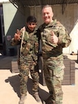 Army Command Sgt. Maj. John Wayne Troxell, the senior enlisted advisor to the chairman of the Joint Chiefs of Staff, poses with a young Syrian Democratic Forces soldier near Kobani, Syria, April 4, 2017.