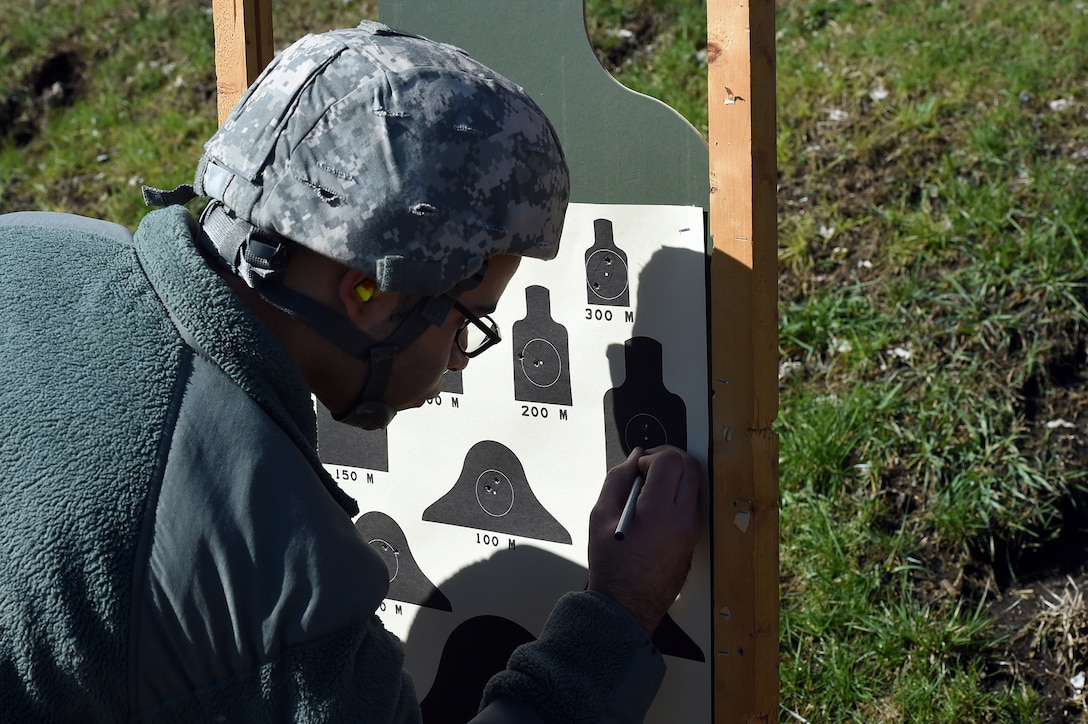 Army Reserve Spc. Matthew Kelly, Human Resources Specialist, 85th Support Command, reviews his qualification performance during the 85th Support Command's headquarters individual weapons qualification at Joliet Training Area, April 1, 2017. The headquarters staff spent one battle assembly day at the qualification range achieving a 100 percent qualification rate on the M-16 rifle and an 88 percent qualification rate on the M9 pistol. Kelly qualified with 34 out of 40 targets hit.