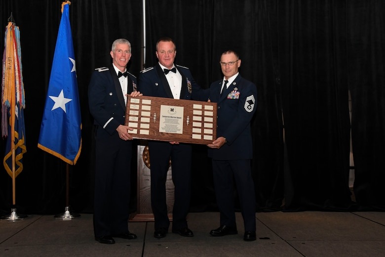 Col. Bruce R. Cox, 307th Bomb Wing commander, presents Col. James Morriss, 307th Bomb Wing vice commander, and Chief Master Sgt. Vernon Cox, 307th Maintenance Group, with the Zamperini Warrior Award during the 307th Bomb Wing's 75th Anniversary and Awards Gala at the Shreveport Convention Center April 1, 2017. (U.S. Air Force photo by Staff Sgt. Callie Ware/Released)