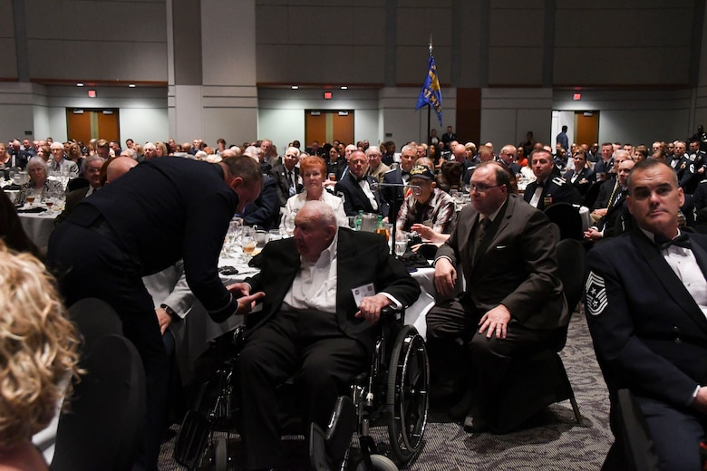 """Col. Bruce R. Cox, 307th Bomb Wing commander, presents Earl McGuier, World War II 307th Bombardment Group veteran, with a Commander's Coin during the 307th Bomb Wing's 75th Anniversary and Awards Gala at the Shreveport Convention Center April 1, 2017. In 1942, 27 B-24 Liberators from the 307th Bombardment Group took part in one of the longest mass-raids of that era which earned them the name """"The Long Rangers."""" The now, 307th Bomb Wing celebrated their 75th Anniversary with alumni from wars such as World War II, Korean War, Vietnam and Operation Inherent Resolve. (U.S. Air Force photo by Staff Sgt. Callie Ware/Released)"""