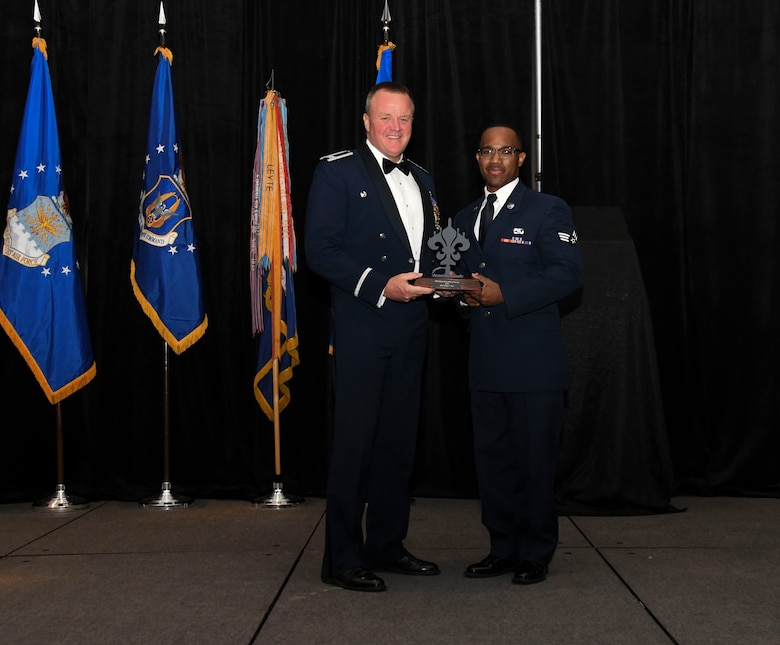 Col. Bruce R. Cox, 307th Bomb Wing commander, presents Senior Airman Timothy Rice, 707th Maintenance Squadron, the 307th Bomb Wing's Airman of the Year award for 2016. The award was presented during the 307th Bomb Wing's 75th Anniversary and Awards Gala at the Shreveport Convention Center April 1, 2017. (U.S. Air Force photo by Staff Sgt. Callie Ware/Released)