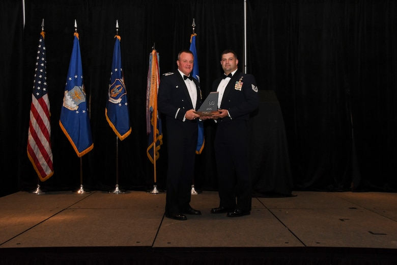 Col. Bruce R. Cox, 307th Bomb Wing commander, presents Tech. Sgt. Marvin Bell, 307th Operations Support Squadron, the 307th Bomb Wing's Non-Commissioned Officer of the Year award for 2016. The award was presented during the 307th Bomb Wing's 75th Anniversary and Awards Gala at the Shreveport Convention Center April 1, 2017. (U.S. Air Force photo by Staff Sgt. Callie Ware/Released)