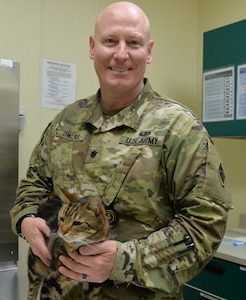 Lt. Col. Douglas Owens, U.S. Army Medical Department Center and School Department of Veterinary Science Animal Health Branch chief, poses with Steve, a domestic shorthair cat, at the AMEDDC&S Veterinary Training Center, Animal Health Branch, at Joint Base San Antonio-Fort Sam Houston. Steve is one of several retiring government-owned animals, dogs and cats, who are being put up for adoption so they can be placed in a new home.
