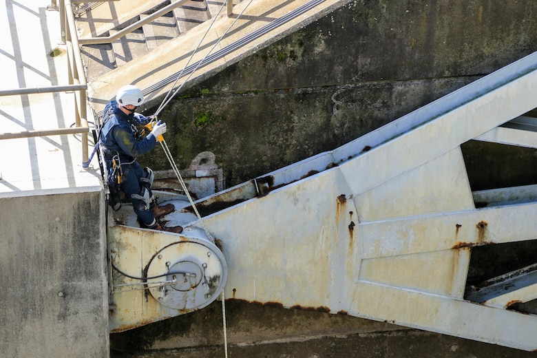 David Jarvis, an engineer with the U.S. Army Corps of Engineers - Tulsa District, inspects the gates on R.S. Kerr Lock and Dam (#15) as part of a periodic inspection.  Jarvis is using the rope access technique, which allows him access to areas he would not have easily accessed by using the fall arrest method.  Rope access allows the inspectors to ascend and descend via ropes, while fall arrest requires them to scale the structure with only a safety line to keep them from falling. (photo by Thomas Mills USACE)