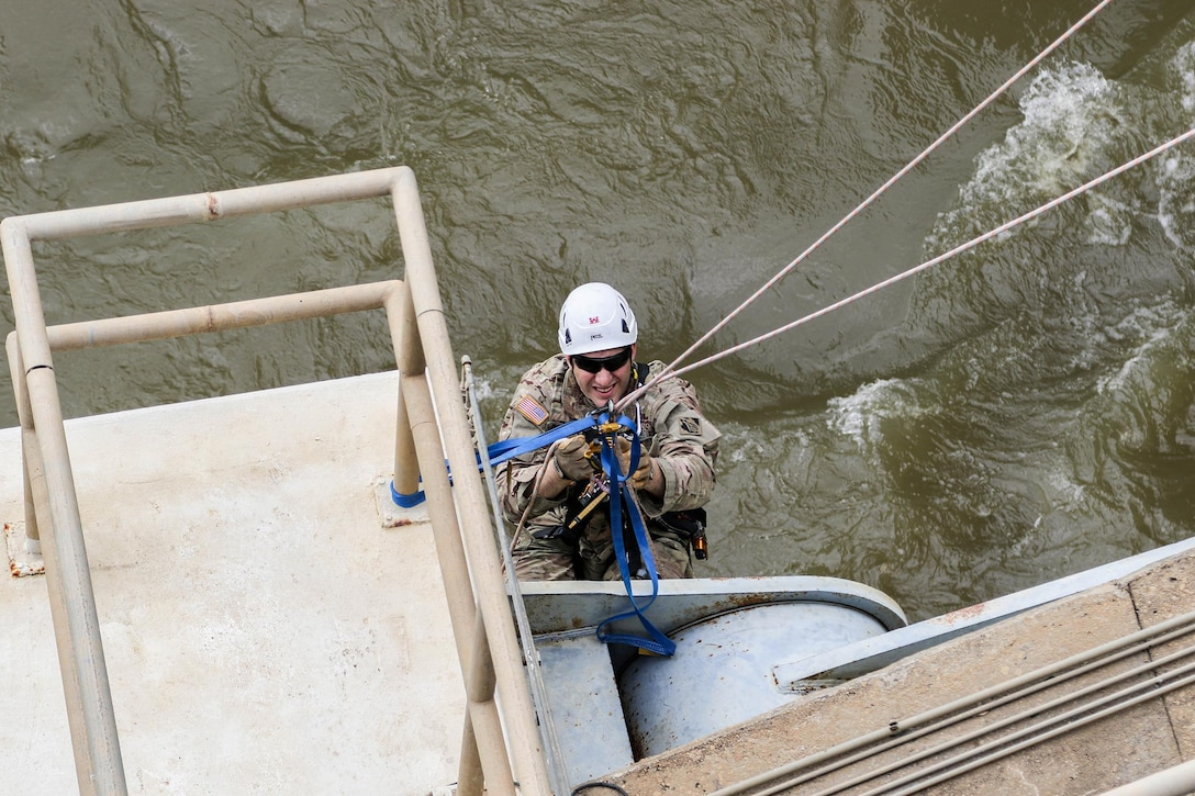 Major Doug Droesch, an engineer with the U.S. Army Corps of Engineers - Tulsa District, inspects the gates on R.S. Kerr Lock and Dam (#15) as part of a periodic inspection.  Droesch is using the rope access technique, which allows him access to areas he would not have easily accessed by using the fall arrest method.  Rope access allows the inspectors to ascend and descend via ropes, while fall arrest requires them to scale the structure with only a safety line to keep them from falling. (photo by Thomas Mills USACE)