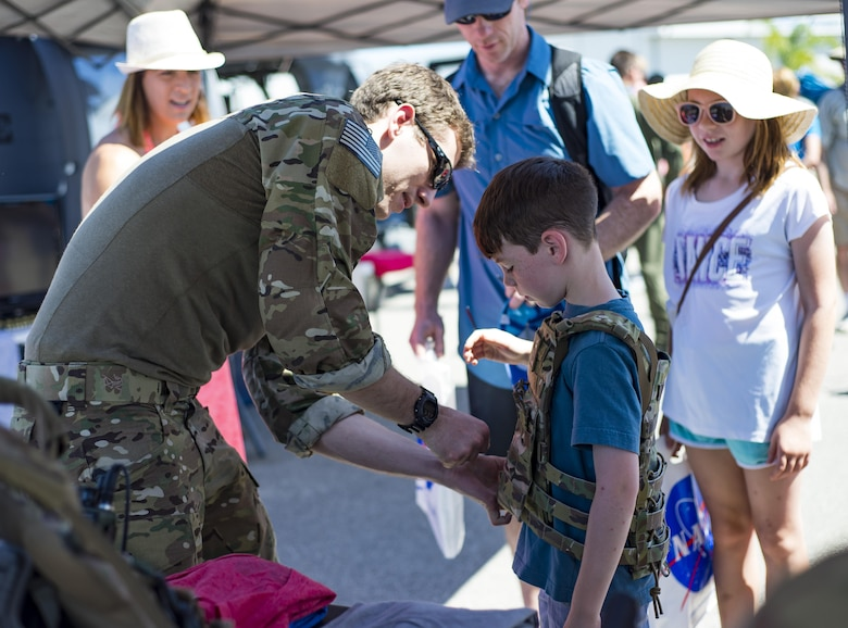 Staff Sgt. Steven Reibitz, a pararescueman from the 308th Rescue Squadron, helps a visitor into a custom body armor plate during the Melbourne Air & Space Show April 1, 2017, at Melbourne, Fla. Airmen from the 920th Rescue Wing displayed the helicopter and equipment used to accomplish the combat search-and-rescue mission. The airshow attracted nearly 200,000 participants and showcased both military and civilian aircraft. (U.S. Air Force photo/Staff Sgt. Jared Trimarchi)