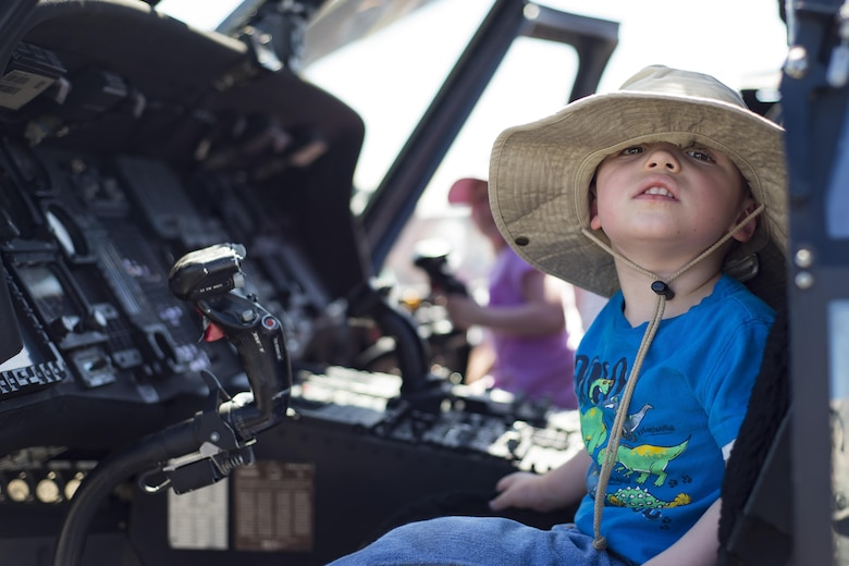 A young spectator smiles in the pilot seat of an HH-60G Pave Hawk during the Melbourne Air & Space Show April 1, 2017, in Melbourne, Fla. Airmen from the 920th Rescue Wing displayed the helicopter and equipment used to accomplish the combat search-and-rescue mission. The airshow attracted nearly 200,000 participants and showcased both military and civilian aircraft. (U.S. Air Force photo/Staff Sgt. Jared Trimarchi)