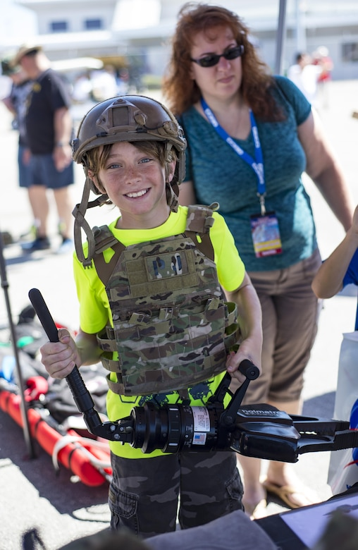 A visitor poses with a helmet, body armor and a hydraulic rescue tool during the Melbourne Air & Space Show April 1, 2017, at Melbourne, Fla. Airmen from the 920th Rescue Wing displayed the helicopter and equipment used to accomplish the combat search-and-rescue mission. The airshow attracted more than 10,000 participants and showcased both military and civilian aircraft. (U.S. Air Force photo/Staff Sgt. Jared Trimarchi)