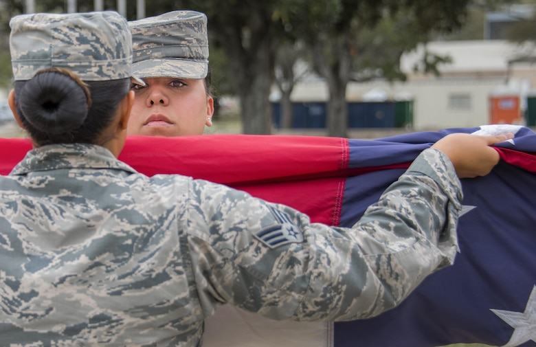 Senior Airman Jamela Shannon, 96th Medical Group, holds up the American flag during the flag-folding portion of a base retreat ceremony March 30, 2017, at Eglin Air Force Base, Fla. The formation and flag detail were comprised of women in honor of Women's History Month. (U.S. Air Force photo/Samuel King Jr.)