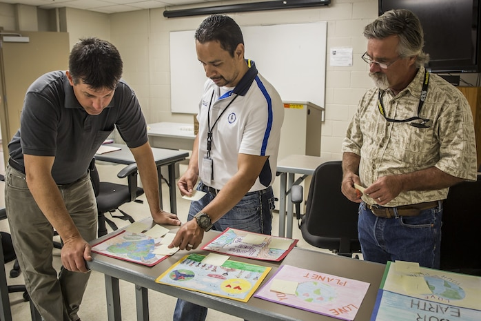 Judges critique the Laurel Bay schools Earth Day posters aboard Marine Corps Air Station Beaufort, April 4. The Natural Resources and Environmental Affairs Office holds the contest in the schools annually to promote healthy environmental management at an early age. The environmental specialists are with NREAO, MCAS Beaufort.