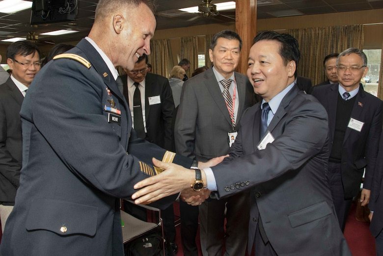 Lt. Gen. Michael C. Wehr (left), President of the Mississippi River Commission, greets Dr. Tran Hong Ha (right), Vietnam's Minister of Natural Resource and Environment, aboard the Corps of Engineers' Motor Vessel Mississippi.