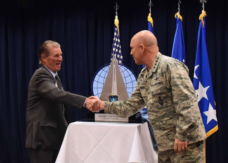 U.S. Air Force Gen. Jay Raymond, Commander, Air Force Space Command, shakes hands with Mr. Michael Jackson of the South Bay Association of Chambers of Commerce, during a ceremony to present the 2016 Air Force Space Command Community Support Award in El Segundo, Calif., Feb. 15, 2017.  The SBACC was named the recipient of the 2016 Air Force Space Command Community Support Award for their outstanding support to the mission and personnel of SMC and Los Angeles Air Force Base. (U.S. Air Force photo by Sarah Corrice)