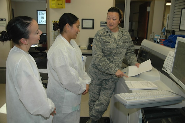 Capt. Dorothy Ridenour, chief of the 61st Medical Squadron's Diagnostic Element at Los Angeles Air Force Base in El Segundo, California, shares the results of chemistry linearity studies from the College of American Pathologists to Staff Sgt. Laurie-Mhae Turla, center, and Senior Airman Jennifer Toney, 61st MDS medical laboratory technicians. The 61st MDS laboratory recently passed a no-notice inspection from the leading organization of board-certified pathologists. The CAP inspector stated it was the highest performing lab ever seen, rating it in the top one-half percent of all labs nationally. (U.S. Air Force photo / Jim Spellman)
