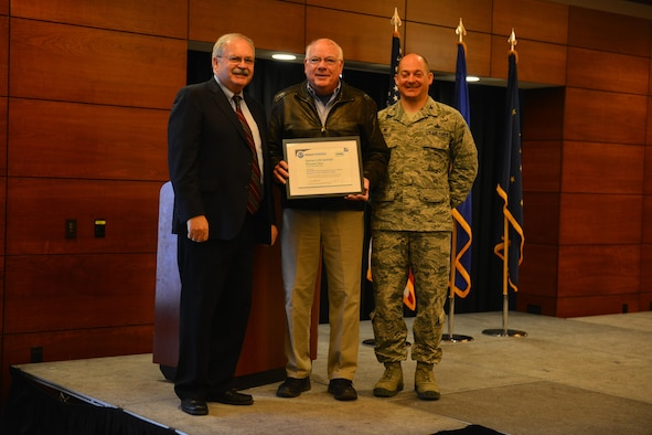 Doug Mecum, Deputy Regional Administrator for the National Oceanic and Atmospheric Association Fisheries in Alaska and Air Force Col. George T.M. Dietrich III, the JBER commander and 673d Air Base Wing commander awards Richard Graham, with the 673d Civil Engineer Squadron a plaque in recognition of JBER being the NOAA's Species in the Spotlight Recovery Hero. NOAA chose to recognize JBER first because of the effectiveness of their ongoing partnership over the past thirty years.