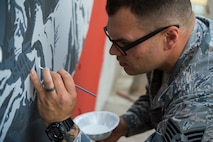 Staff Sgt. Jonathan, a 380th Expeditionary Civil Engineer Squadron firefighter, paints the final touches on a mural at an undisclosed location in Southwest Asia, March 6, 2017. Johnathan dedicated more than 150 hours during his off-duty time to complete the mural while supporting Combined Joint Task Force-Operation Inherent Resolve. (U.S. Air Force photo/Senior Airman Tyler Woodward)